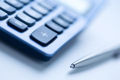 Calculator. And pen in blue color, shallow focus Royalty Free Stock Photography