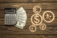 Calculator, American dollar banknotes of currency signs, businessman runs in gears. On a wooden background stock photos