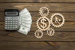 Calculator, American dollar bills currency signs, running worker with a suitcase in gears. On a wooden background stock images