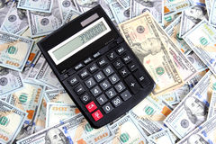 Calculator on background of hundred dollar bills Royalty Free Stock Photos