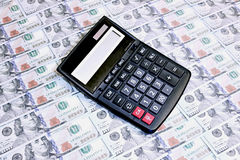 Calculator on background of hundred dollar bills Royalty Free Stock Images