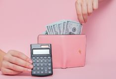 Calculator on background with Woman`s hand removing money from wallet on the pink background with copy space stock photos