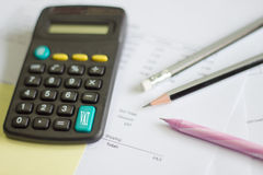 A calculator is on a balance sheet numbers are statistics. photo Stock Photos