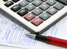 Calculator, ball pen, and hand-written text Royalty Free Stock Photo