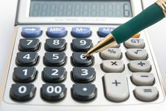 Calculator and a ballpoint. Calculator and a green ballpoint stock photography
