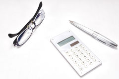Calculator and ballpoint and glasses Stock Photo
