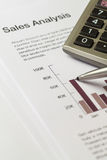 Calculator and ballpoint pen on sales charts Royalty Free Stock Images