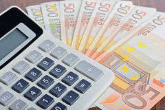 Calculator and banknotes on the table Stock Image