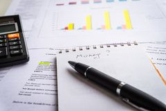 Calculator and black pen with accounting report and financial statement on desk royalty free stock images