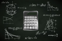 Calculator on blackboard with math calculations  Royalty Free Stock Photography