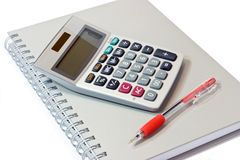 Calculator with book and pen Stock Images