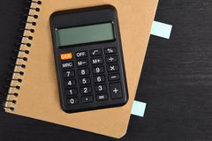 Calculator. Brown Notepad with calculator on black wooden background Royalty Free Stock Image