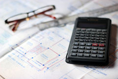 Calculator and building plans. Stock Images