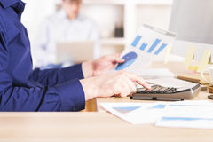 Calculator on business diagrams. Sideview of businessman using calculator on business diagrams royalty free stock photo