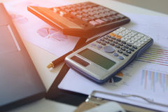 Calculator with business graphs and charts report on tabble, calculator on desk of financial planing. Financial background concept. Calculator with business Royalty Free Stock Photos