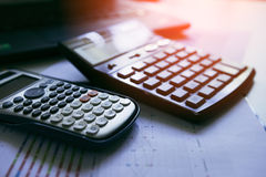Calculator with business graphs and charts report on table, calculator on desk of financial planing. Financial concepts. Calculator with business graphs and Stock Photography