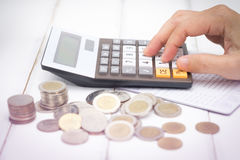 Calculator. Businesswoman using a calculator  have saving Account Book from Bank for Business Finance with pen, calculator and coin on desk, Choose focus point Royalty Free Stock Photo