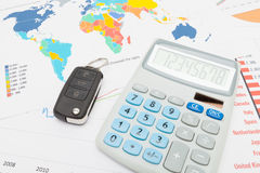 Calculator and car keys over world map Stock Photo