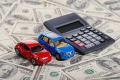 Calculator and car toys through the dollars. Calculator and car toys among the dollars (Installation on the theme of car purchasing and auto credit Stock Photo