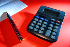 Calculator and Checkbook Bank Register. Calculator with ballpoint pen on a bank account checkbook register on red surface stock image