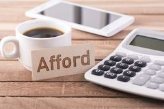 The word afford. Calculator, coffee and mobile with the word afford written in card on wooden table Royalty Free Stock Photography