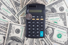 Calculator and coin ruble on the background of banknotes dollars Royalty Free Stock Photography