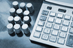 Calculator and coins Stock Images