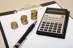 Calculator and coins. On table Royalty Free Stock Photos