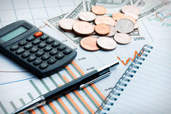 Calculator and coins on business graph. Royalty Free Stock Photo