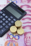 Calculator and coins on chinese currency Royalty Free Stock Photo