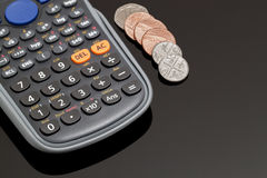 Finance. Calculator and Coins on a Desktop with Black Glass Stock Images