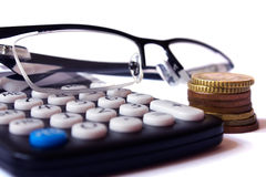 Calculator, coins and glasses Stock Photos
