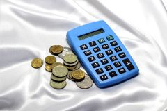 Calculator and coins on a white background. Royalty Free Stock Image