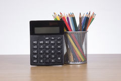 Calculator with colored pencils in container Royalty Free Stock Images