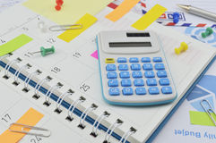 Calculator with colorful post It notes on business diary page Royalty Free Stock Image