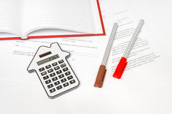 Calculator and contract - mortgage and real estate concept. Calculator and contract on table - mortgage, real estate and buying house concept Royalty Free Stock Images