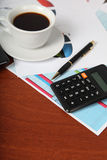 Calculator and cup of coffee Stock Images