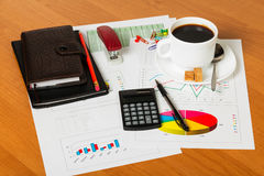 Calculator, cup coffee, notebooks and other stationery to desktop background. Royalty Free Stock Image