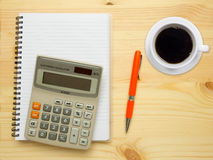 Calculator, a cup of coffee, pen and notebook. Stock Image