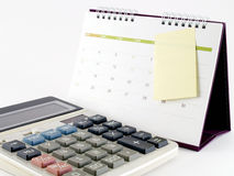 white calculator with desk calendar and blank sticky note taped on the calendar page in April 2016 Royalty Free Stock Images