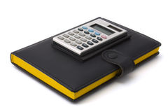 Calculator and diary. Calculator on a diary. The diary in black leather cover with bright yellow pages stock image
