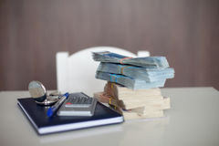 Calculator with diary, euro bills and pen, lying on a table Stock Photos