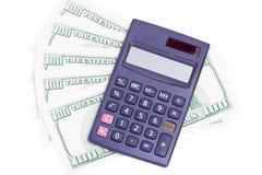 Calculator on dollar bills. Calculator on hundred dollar bills over white background Royalty Free Stock Images