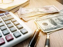 Calculator, dollar bills and accounting book on a table. Stock Image