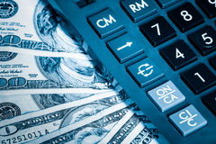 Calculator and dollar bills toned in blue Royalty Free Stock Photography
