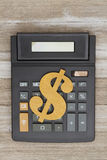 Calculator with a dollar sign on weathered wood royalty free stock image