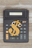 Calculator with a dollar sign on weathered wood stock image