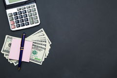 Calculator and Dollars on black background Stock Photos