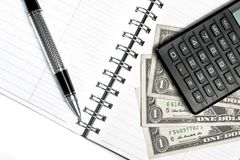 Calculator, dollars and business pen on notebook Stock Image