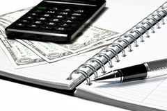 Calculator, dollars and business pen on notebook Stock Photo